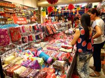 Tourists choose from a variety of souvenir products at a store or shop in Chinatown, Singapore. Stock Photography