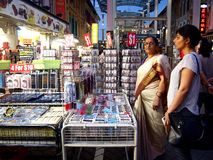Tourists choose from a variety of souvenir products at a store or shop in Chinatown, Singapore. Stock Images