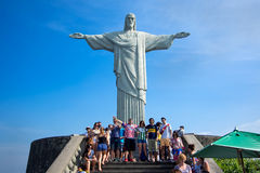 Tourists at Christ the Redeemer Statue, Rio de Janeiro, Brazil. Tourists posing in front of famous Christ the Redeemer staue atop the Corcovado mountain in Rio Royalty Free Stock Photography
