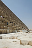 Tourists clamberig on the ruined wall of an Egyptian pyramid Royalty Free Stock Photo