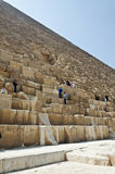 Tourists clamberig on the ruined wall of an Egyptian pyramid Stock Photo