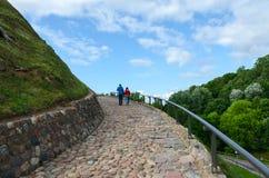 Tourists climb on mountain of Gediminas along serpentine road Stock Photo
