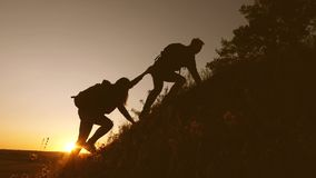 Tourists climb the mountain in sunset, holding hands. male traveler holds out his hand to a female traveler climbing a stock video footage