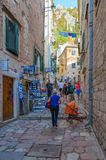 Tourists climb narrow street of Old City to fortress, Kotor, Montenegro. KOTOR, MONTENEGRO - SEPTEMBER 8, 2017: Unknown tourists climb narrow street of Old City Stock Image