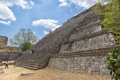 Tourists climb pyramid in Mexico. April 23, 2014 Uxmal, Mexico: tourists climb the steep stairs of a pyramid at the UNESCO World Heritage site Royalty Free Stock Photography