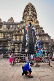Tourists climb the steep steps to the highest temple of Angkor W Royalty Free Stock Photography