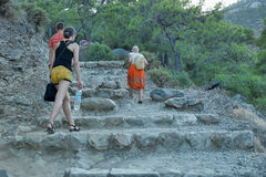 Tourists climb the stone steps carved into the rock Royalty Free Stock Image