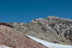 Tourists and Climbers Walking in Stone Path among Barren Mountai Royalty Free Stock Photos