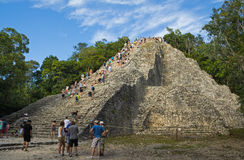 Tourists are climbing on the highest pyramid of Yucatan stock images