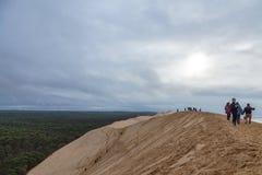 Tourists climbing the Pilat Dune Dune du Pilat during a cloudy afternoon. PILAT, FRANCE - DECEMBER 28, 2017: Tourists climbing the Pilat Dune Dune du Pilat Stock Photo