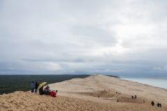Tourists climbing the Pilat Dune Dune du Pilat during a cloudy afternoon. PILAT, FRANCE - DECEMBER 28, 2017: Tourists climbing the Pilat Dune Dune du Pilat Royalty Free Stock Image