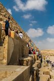 Tourists climbing the pyramids of Giza, Egypt