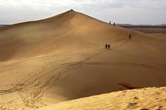 Tourists climbing a sand dune Stock Image