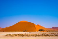 Tourists climbing sand dune at Sossusvlei, Namib desert, Namib Naukluft National Park, Namibia. Traveling people, adventure and va Stock Images
