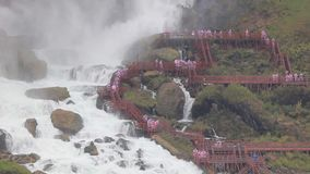 Tourists at the American Falls, United States. Tourists climbing the stairs down to the Waterfalls viewing platform and getting wet. American Falls at the stock footage