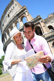 Tourists by the Coliseum. Couple in Rome reading guide book by the Coliseum Royalty Free Stock Photos