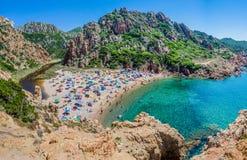 Tourists colorful sun umbrellas at Costa Paradiso Beach, Sardinia, Italy.  stock photo