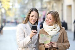 Tourists comparing phone and map in winter holiday. Front view of two happy tourists comparing smart phone contant and paper map in winter holiday in the street stock photography