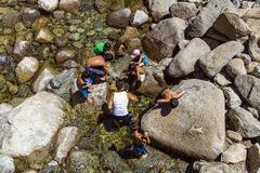 Tourists cool their legs in the lake of the lower Yosemite wate Royalty Free Stock Image