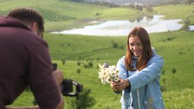Tourists couple enjoying the nature, young man taking photo of happy woman holding bouquet of field flowers. slow motion. Tourists couple enjoying the nature stock video footage