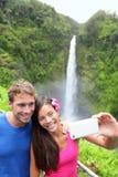 Tourists couple taking photo on Hawaii. Tourists couple taking self portrait photo on Hawaii with camera phone on Hawaii, Big Islands, Akaka Falls. Happy Stock Photo