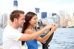 Tourists couple travel in New York. Beautiful young interracial young couple on travel looking at Manhattan and New York City skyline from Ellis Island. Asian Royalty Free Stock Photos