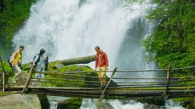 Tourists cross the river on a background of a waterfall. Doi Inthanon National park, Thailand stock footage
