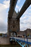 Tourists crossing the Tower Bridge of London, Europe. Blue sky and clouds background Royalty Free Stock Photo