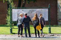 Tourists crowd around the map of the fortress on the paved area. Royalty Free Stock Image