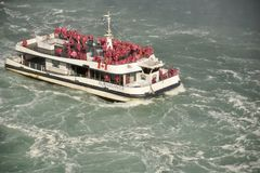 Tourists Crowd the decks of the Hornblower Ferry Boat on the Niagara River. The Hornblower struggles against the powerful current as it takes its passengers for royalty free stock photos
