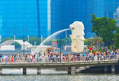 Tourists crowd by Singapore Lion. SINGAPORE - JANUARY 14, 2017: Crowd of tourists by Singapore Lion fountain, glass facades of skyscrapers in background stock images