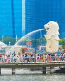 Tourists crowd by Singapore Lion. SINGAPORE - JANUARY 14, 2017: Crowd of tourists by Singapore Lion fountain, glass facades of skyscrapers in background stock photos
