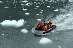 Tourists from the cruise ship in the Garibaldi fjord in the archipelago of Tierra del Fuego. TIERRA DEL FUEGO, CHILE - NOVEMBER 19,2014: Tourists from the royalty free stock images