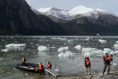 Tourists from the cruise ship landed on the shore near Pia glacier. Royalty Free Stock Photography