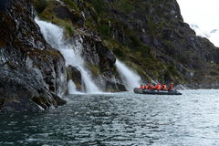Tourists from the cruise ship near the waterfalls of the glacier Nena. Royalty Free Stock Image