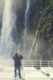 Tourists on the cruising boat approaching Stirling Falls , Milford Sound, Fiordland, South Island of New Zealand royalty free stock image