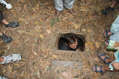 Tourists at Cu Chi Tunnels Vietnam. Tourist entering the small entrance to the Cu Chi Tunnels outside of Ho Chi Minh City Vietnam-- a series of tunnel used by Stock Image