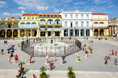 Tourists and cubans at Old Square in Old Havana. HAVANA,CUBA- APRIL 20,2016 : Tourists and cubans at colorful colonial Old Square in the heart of Old Havana Royalty Free Stock Images