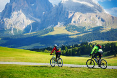 Tourists cycling in Seiser Alm, the largest high altitude Alpine meadow in Europe, stunning rocky mountains on the background. Stock Photos