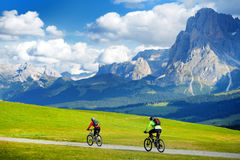 Tourists cycling in Seiser Alm, the largest high altitude Alpine meadow in Europe, stunning rocky mountains on the background. Royalty Free Stock Image