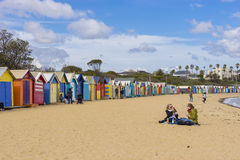 Tourists at Dendy Street Beach, Brighton with colourful bathing houses in Melbourne stock images