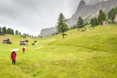 Tourists descend to the valley from the mountains of the Dolomit. Es, Alps, through green fields Stock Image