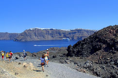 Tourists descending Greek volcanic island. Tourists sightseeing the active volcano  Nea Kameni island and Santorini island in the distance.Picture taken on Stock Images