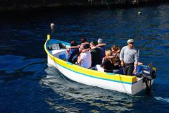Tourists in a Dghajsa, Blue Grotto. Tourists in Dghajsa water taxi boat at the departure point in the bay, Blue Grotto, Malta, Europe Stock Photography