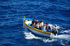 Tourists in a Maltese Dghajsa at Blue Grotto, Malta. Tourists in Dghajsa water taxi boat in the bay, Blue Grotto, Malta, Europe Royalty Free Stock Images