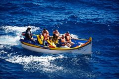 Tourists in a Dghajsa water taxi, Malta. Tourists in Dghajsa water taxi boat in the bay, Blue Grotto, Malta, Europe Royalty Free Stock Photography