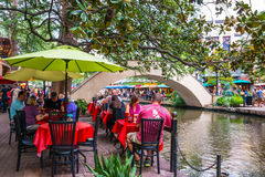 Tourists Dining on River Walk in Evening in San Antonio Texas. SAN ANTONIO, TEXAS - SEPT 20, 2014: Tourists dining at outside cafes with colorful umbrellas near stock images