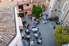 Tourists at dinner in the main square of Castelmola royalty free stock photo