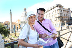 Tourists discovering foro Traiano. Couple in Rome reading guide book by the Foro Traiano Stock Photos