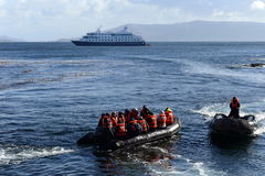 Tourists disembark from cruise ship on Cape horn. CAPE HORN, CHILE - NOVEMBER 18,2014: Tourists disembark from cruise ship on Cape horn. Cape Horn - the Stock Image